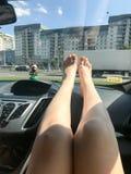 Le belle gambe lunghe esili femminili con un pedicure giallo sulle dita si trovano sul cruscotto dell'automobile fotografia stock libera da diritti