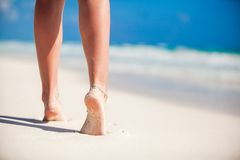 Le belle gambe regolari delle donne sulla spiaggia di sabbia bianca Fotografia Stock
