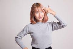 Le belle giovani dita asiatiche della tenuta della donna in pistola gesture immagine stock