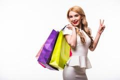 Le belle giovani donne con le borse con la vittoria firmano, concetto di compera su fondo bianco Immagini Stock
