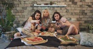 Le belle giovani signore si divertono insieme nella camera da letto in pigiami che giocano su un PlayStation molto archivi video