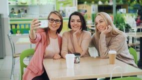 Le belle giovani signore stanno prendendo il selfie facendo uso dello smartphone che si siede alla tavola in caffè e che posa con video d archivio