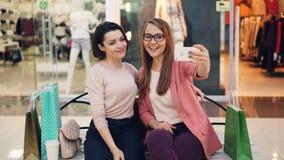 Le belle giovani signore stanno prendendo insieme il selfie facendo uso dello smartphone che si siede nel centro commerciale che  video d archivio