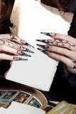 Le belle mani con la strega acrilica lunga anneriscono i chiodi che tengono uno strato bianco nelle mani di fotografia stock libera da diritti