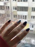 Le belle mani con le unghie del manicure nel rosso hanno tricottato la manica del maglione sul vetro di finestra Immagini Stock Libere da Diritti
