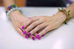 Le belle mani femminili hanno piegato sulla tavola bianca Per mano di bei braccialetti Fotografia Stock