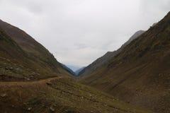 Le belle piste sulle grandi montagne nel Kashmir sotto il cielo nuvoloso scuro fotografie stock libere da diritti