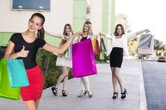 Le belle ragazze con i sacchetti della spesa si avvicinano al centro commerciale Fotografia Stock Libera da Diritti