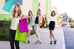 Le belle ragazze con i sacchetti della spesa si avvicinano al centro commerciale Immagine Stock