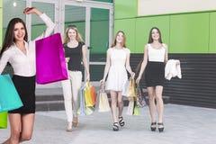 Le belle ragazze con i sacchetti della spesa si avvicinano al centro commerciale Fotografia Stock