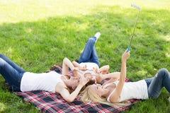 Le belle ragazze nel parco fanno il selfi Fotografia Stock
