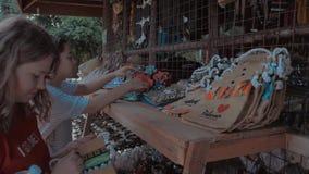 Le belle ragazze sceglie le borse di eco nel mercato di strada asiatico Borsa alla moda di eco della donna Palawan Filippine archivi video