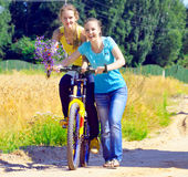 Le belle ragazze sorridenti camminano con la bicicletta sulla villa Fotografia Stock