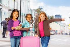 Le belle ragazze stanno con la mappa ed i bagagli in città Immagini Stock