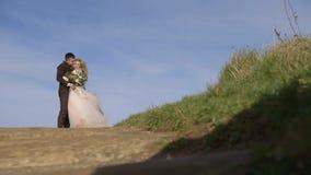 Le belle spose sono fotografate contro il contesto della natura Passeggiate giovani di una coppia archivi video