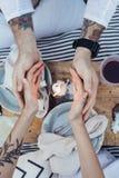 Le belle tenute delle coppie consegna la luce della candela immagine stock