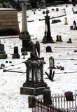 Le belle vecchie pietre tombali hanno sparso sopra terreno collinoso del cimitero Immagine Stock