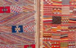 Le Berber marocain coloré tapisse accrocher sur le mur d'adobe Image stock