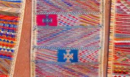 Le Berber marocain coloré tapisse accrocher sur le mur d'adobe Images libres de droits