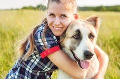 Le berger asiatique central de fille et de chien étreignent en parc Marche avec Image stock