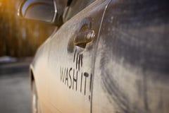 Le besoin très sale de voiture le lavant avec le lavage d'expression sur la rue photographie stock libre de droits
