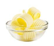 Le beurre s'enroule dans une cuvette en verre Image libre de droits
