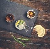 Le bevande alcoliche sull'ardesia imbarcano su fondo di legno rustico Fotografie Stock