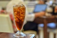 Le bevande di Brown hanno un gusto dolce in tazza di vetro alta sulla tavola di legno con fondo confuso fotografia stock