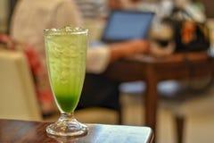 Le bevande verdi hanno un gusto dolce in tazza di vetro alta sulla tavola di legno con fondo confuso immagini stock libere da diritti