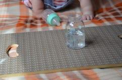 Le biberon avec le wather et la cuillère pour dans le fond de la fourmi de bébé joue Images stock
