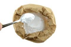 Le bicarbonate de soude contient dedans dans le sac de papier brun, fond d'isolat photos stock