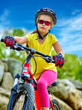 Le bici che ciclano la ragazza nel parco guida la bicicletta sulle montagne Immagine Stock