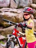 Le bici che ciclano la ragazza in parco guida la bicicletta nelle montagne Fotografie Stock