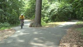 Le bici di camminata e di guida della gente nella città del parco (2 di 3) visitano (x di x) stock footage