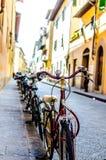 Le biciclette hanno parcheggiato su una pavimentazione su una via stretta Fotografia Stock