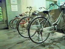 Le biciclette in una fila hanno parcheggiato all'aria aperta, situata a Tokyo Immagini Stock