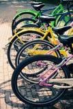 Le biciclette variopinte stanno nella fila su un parcheggio Immagini Stock Libere da Diritti