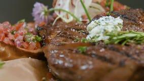 Le bifteck appétissant délicieux de porc a fait cuire sur un plan rapproché de gril avec du fromage et le pain avec l'adjika banque de vidéos