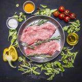 Le bifteck cru de porc sur la salade de poêle de vintage, tomates-cerises, paprika, huile épice la vue supérieure de fond rustiqu Photographie stock libre de droits