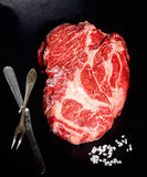 Le bifteck cru a marbré le boeuf, la fourchette de vintage et le couteau sur le fond noir Images libres de droits