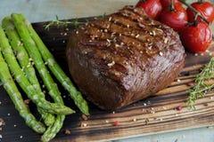 Le bifteck de boeuf a grillé avec l'épice de tomates d'asperge sur une surface en bois Photos libres de droits