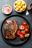 Le bifteck de boeuf grillé a servi du plat de fonte avec de la salade de tomate, les boules de pommes de terre et le vin rouge Ba photo libre de droits
