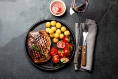 Le bifteck de boeuf grillé a servi du plat de fonte avec de la salade de tomate, les boules de pommes de terre et le vin rouge Ba photos stock