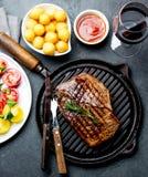Le bifteck de boeuf grillé sur la casserole de gril a servi avec de la salade de tomate, les boules de pommes de terre et le vin  image stock