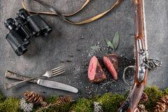 Le bifteck de cerfs communs ou de venaison avec la longs arme à feu, couverts, binoculaire antiques et des ingrédients aiment le  Photos libres de droits