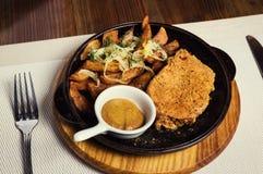 Le bifteck de porc avec les pommes de terre frites a servi dans une poêle servie l'esprit images stock