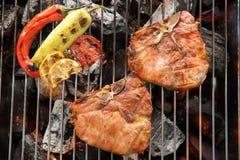 Le bifteck et le légume de côtelette de porc sur un BBQ flamboyant grillent Images stock