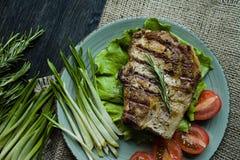 Le bifteck grillé a servi d'un plat, décoré des épices pour la viande, le romarin, les verts et les légumes sur un fond en bois f images libres de droits