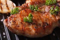 Le bifteck juteux de porc a grillé aux oignons dans un macro de gril de casserole Photographie stock