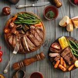 Le bifteck juteux a fait cuire sur un gril avec les légumes grillés photographie stock